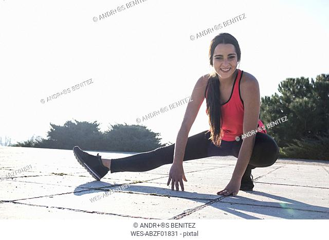 Smiling young woman stretching before running