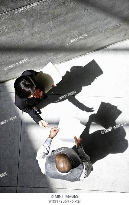View looking down on a businesswoman and businessman talking in an office building lobby