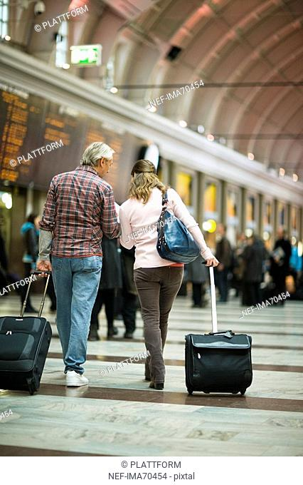 A couple with suitcases at a railway station Sweden