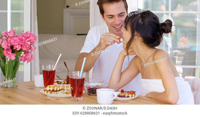 Man feeding his wife fruit at breakfast