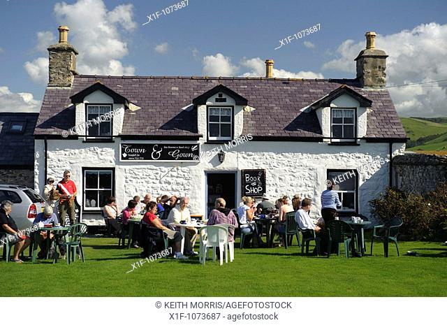 People sitting outside the Town and Gown tearooms and bookshop, sunny september afternon, Tywyn Gwynedd north wales UK