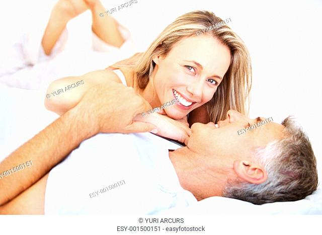 Portrait of couple relaxing in bedroom and smiling