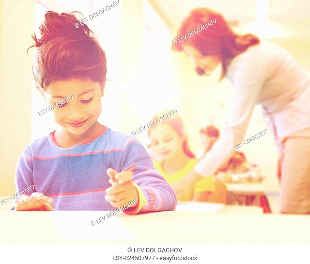 education, elementary school and children concept - happy little student girl with pen and paper writing over classrom and teacher background