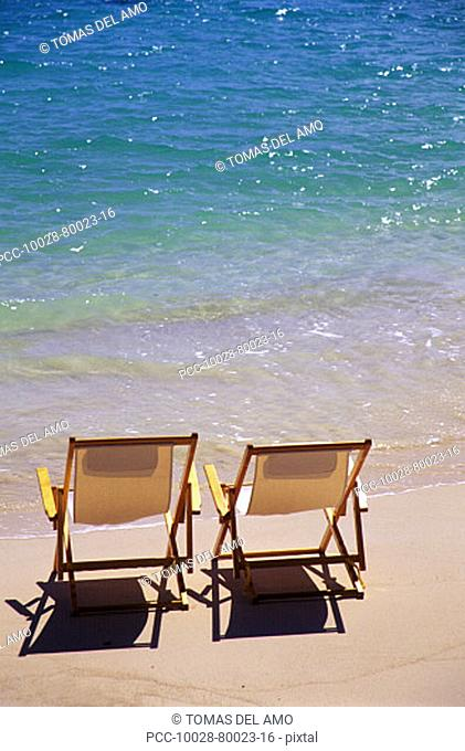 Beach chairs on the shoreline of a tropical beach, calm waves washing ashore, turquoise water