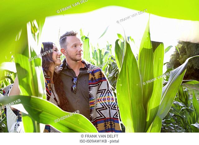 Couple looking out from field of corn plants