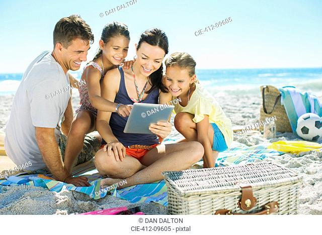 Family using digital tablet on beach