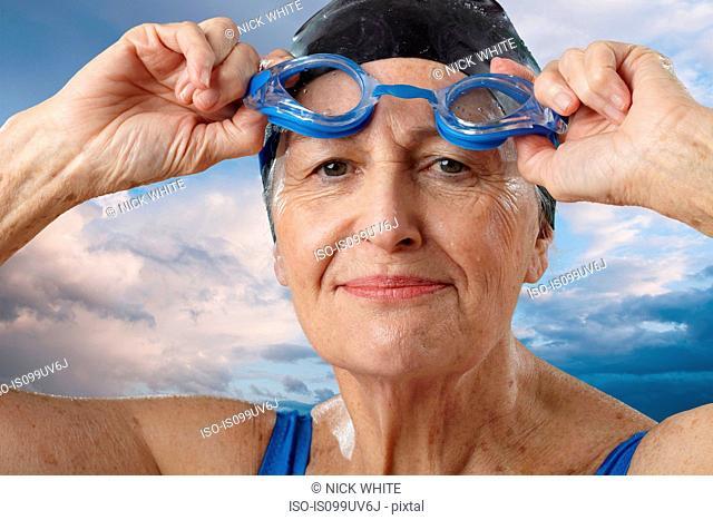 Senior woman adjusting swimming goggles