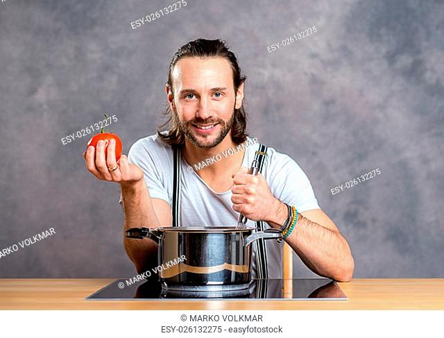 young bearded man with cooking pot and tomato in front of gray background