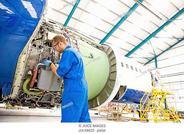 Engineer assembling engine on passenger jet in hangar