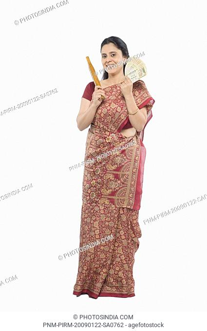 Woman holding currency notes and a rolling pin