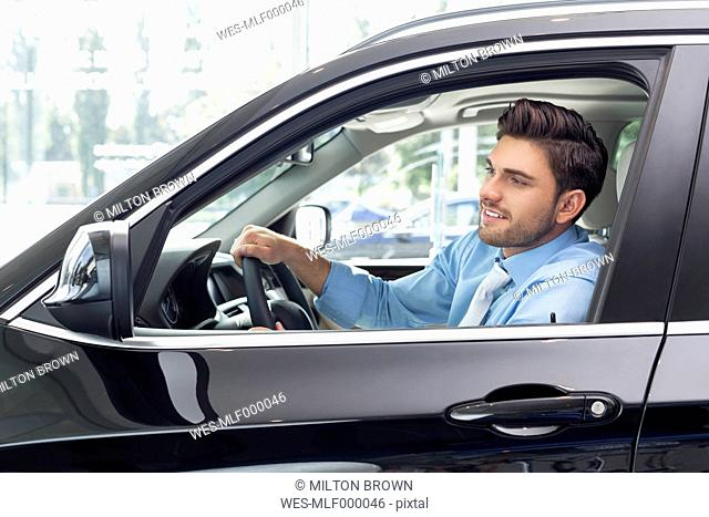 At the car dealer, Man sitting in new car