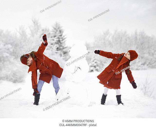 Girls building snowman outdoors
