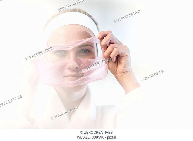 Young woman at spa removing facial mask
