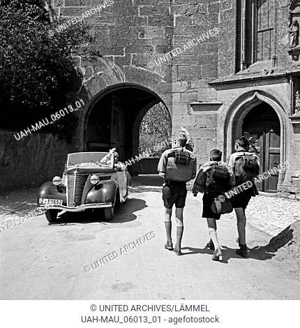 Drei Hitlerjungen auf einer Wandertour durch Deutschland begegnen einem Ford Eifel, 1930er Jahre. Three Hitler youths wandering through Germany seeing a Ford...