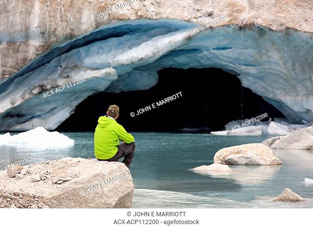 Hiker looking at an ice cave at the toe of the Dartmouth Glacier, BC, Canada