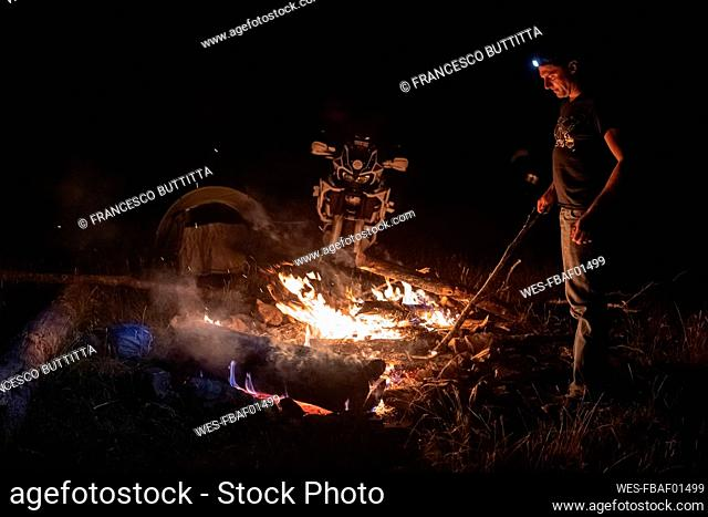 Man on a motorbike trip at night at camp fire