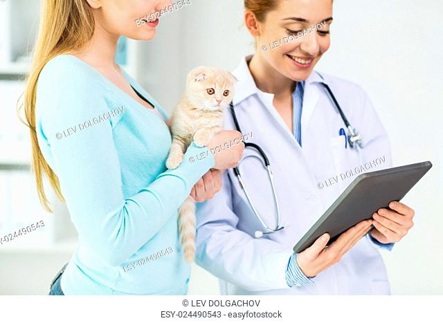medicine, pet, health care, technology and people concept - close up of happy woman and veterinarian doctor with tablet pc computer checking scottish fold...