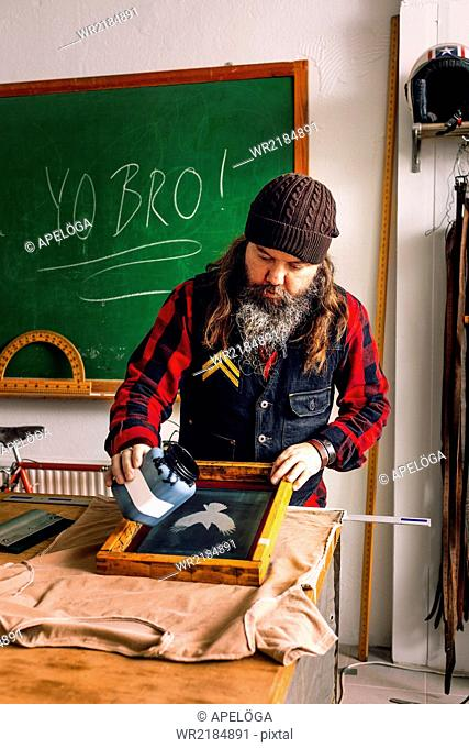 Mature male worker pouring ink on screen printing frame at workshop