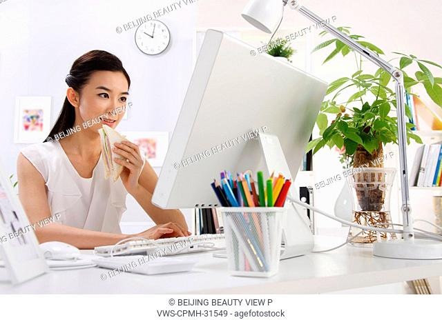 Woman eating sandwich with computer