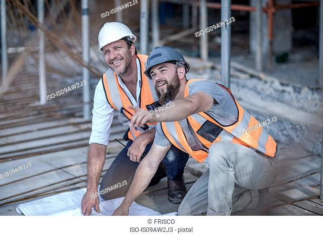 Site manager and builder with blueprint on construction site