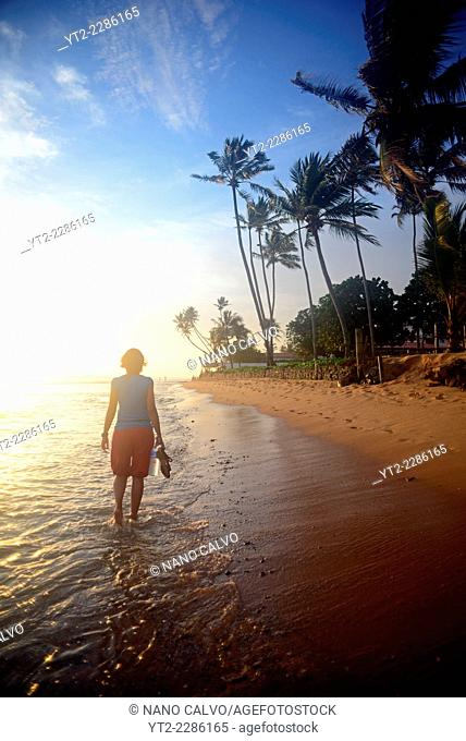 Young woman walking on Hikkaduwa beach at sunset, Sri Lanka