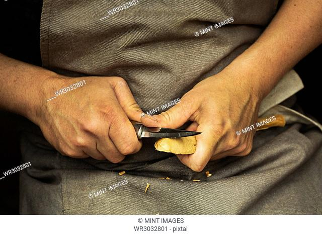 Close up of a craftsman's hands pressing and shaping a small piece of wood into a spoon with a sharp knife blade, shaping the bowl back