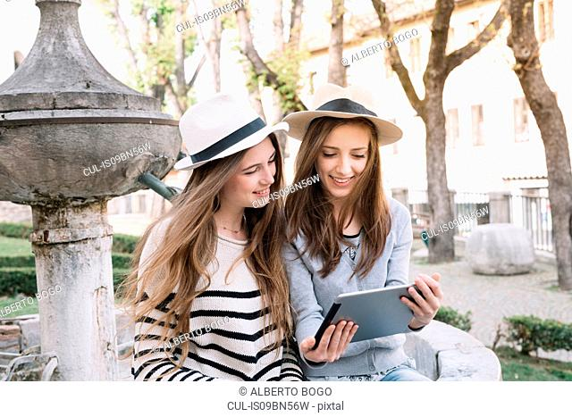 Girlfriends using digital tablet at piazza, Belluno, Veneto, Italy