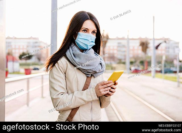 Mid adult woman with protective face mask looking away while holding mobile phone at railroad station