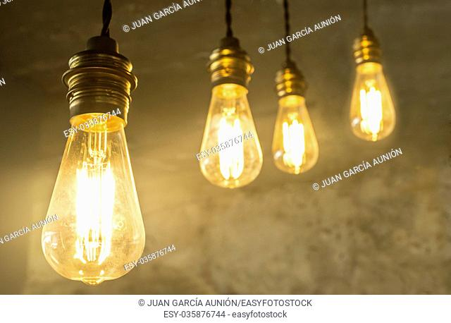 Four hanging light bulbs over oxide dark color concrete background. Closeup