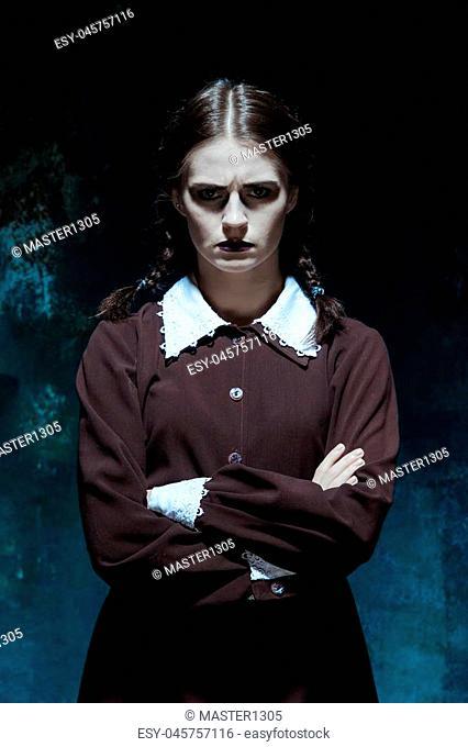 Portrait of a young girl in school uniform as killer woman against school board