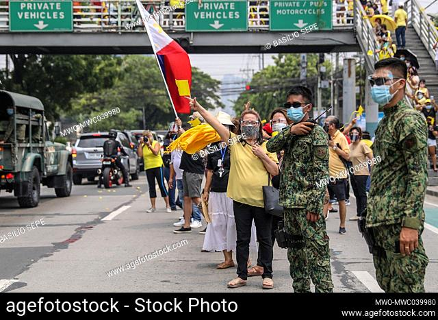Supporters gather beside the motorcade of former Philippine President Benigno Aquino III before his burial in Quezon City, Philippines