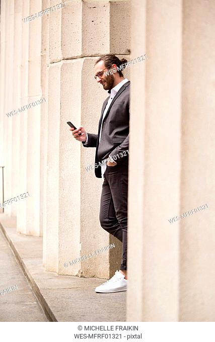 Young businessman standing among columns of Stock Exchange looking at cell phone, New York City, USA