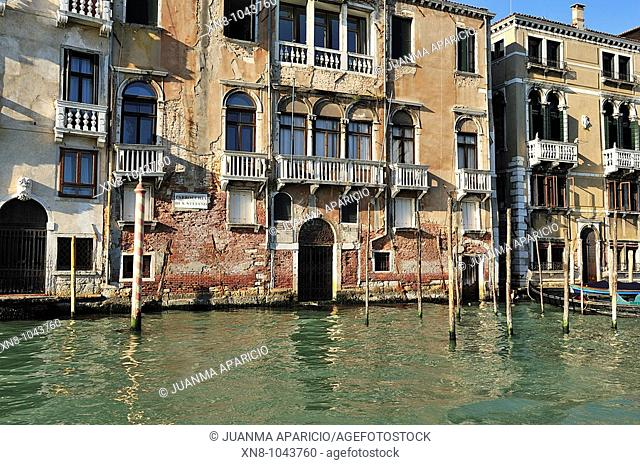 Facade of the Parish of St. Stephen in the Grand Canal in Venice with red brick in sight in poor condition due to moisture