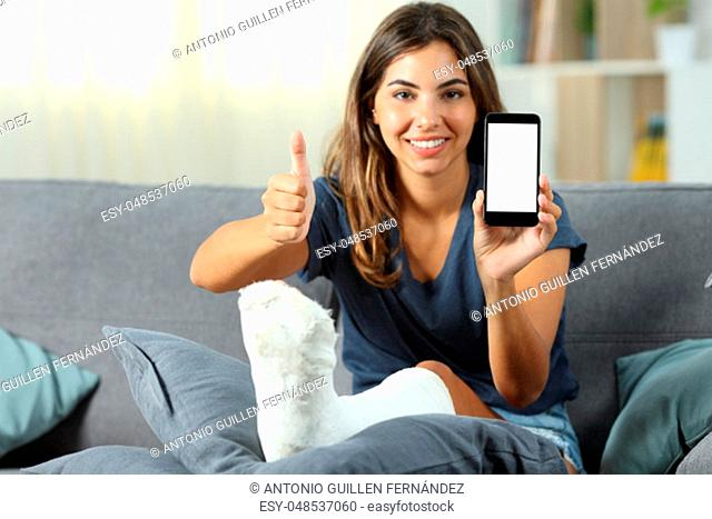 Disabled girl showing a blank phone screen with thumbs up sitting on a couch in the living room at home