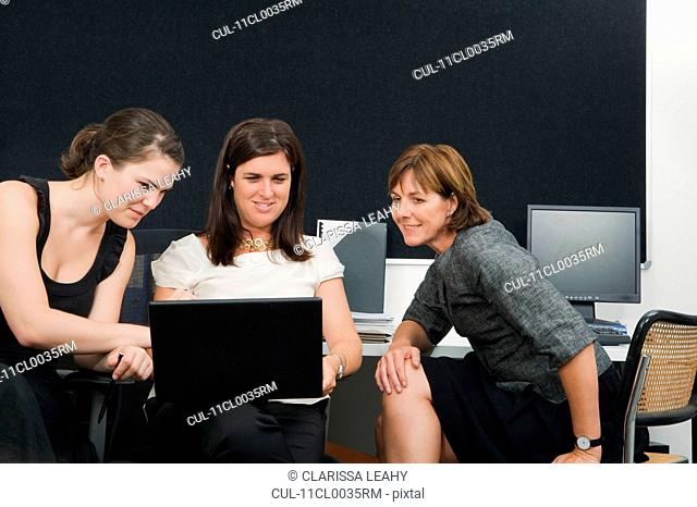 Women colleagues looking at laptop