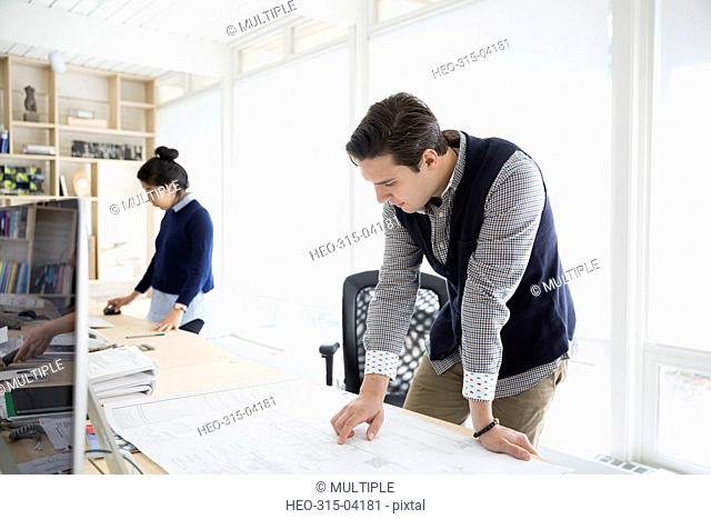 Male architect reviewing blueprint in office