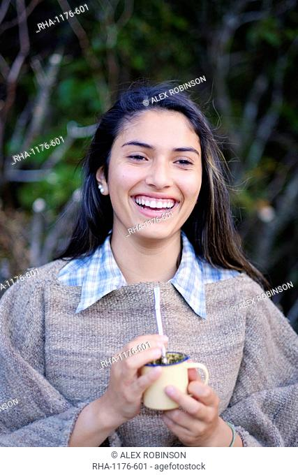 A Patagonian girl in a traditional wool poncho with a bombilla straw drinking yerba mate, Patagonia, Chile, South America