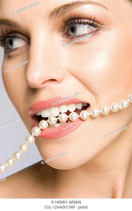 Female beauty model with pearls in mouth