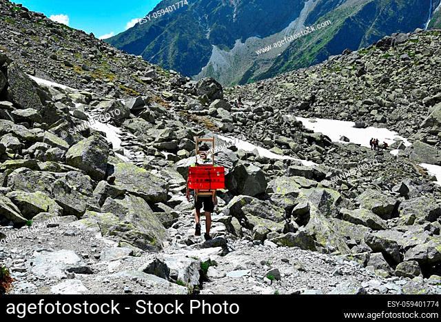 A man carrying boxes down from the mountain lodge Chata pod Rysmi near mount Rysy. High Tatras, Slovakia