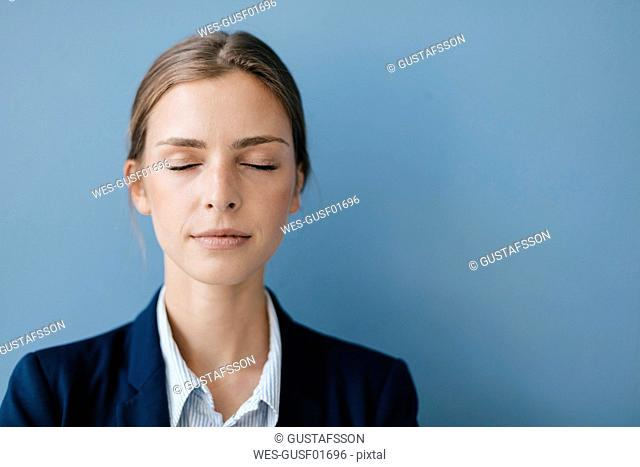 Portrait of a young businesswoman against blue background, relaxing with eyes closed
