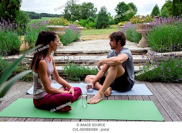 Man and woman practicing yoga in garden, taking a break on patio