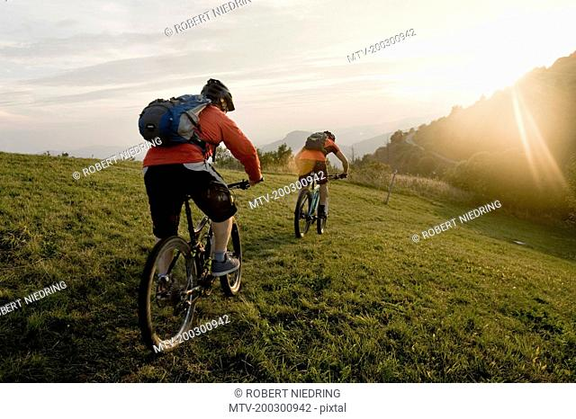two mountain bikers on the way at sunset, Kolovrat, Istria, Slovenia