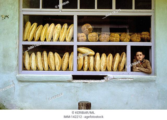 Turkey, North East Anatolia illstrn Istanbul, Beykoz, bakery, loaves of bread, young boy stands at window