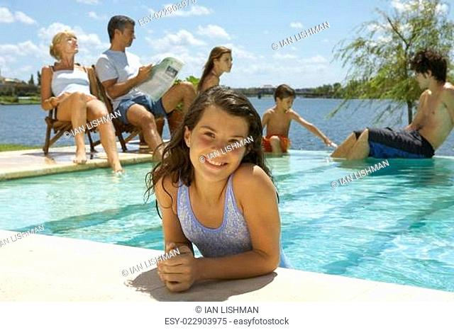 A girl in the pool, family in the background