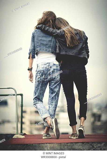 rear view of young woman standing on a rooftop with their arms around each other