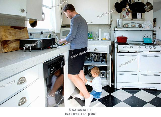 Father in kitchen, washing up, young son on ground beside him
