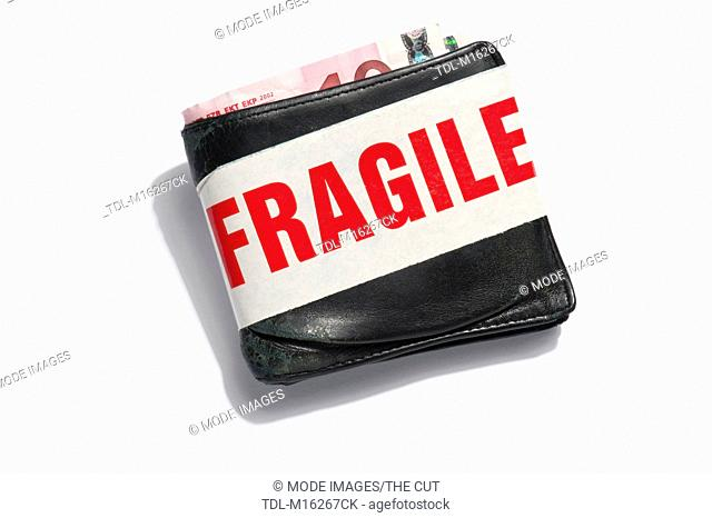 An old leather wallet containing euros with fragile tape around it