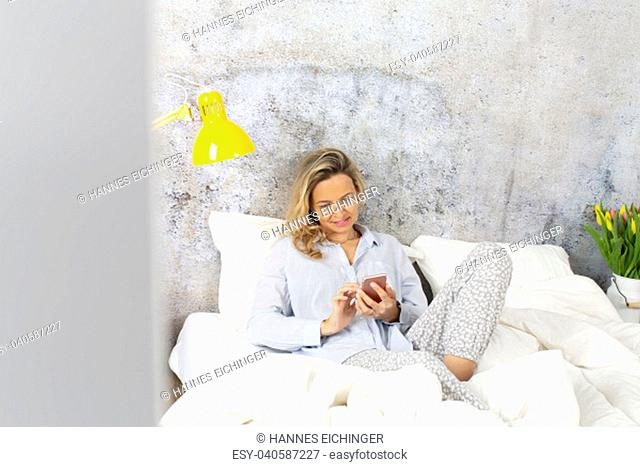 beautiful woman in the morning in bed with smartphone