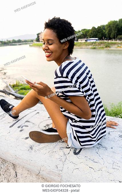 Smiling young woman sitting on wall at the riverside using cell phone
