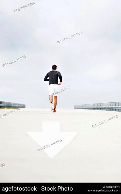 Young man running on a lane
